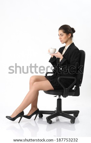 Business woman sitting in an office chair to relax with a cup of coffee on white background - stock photo