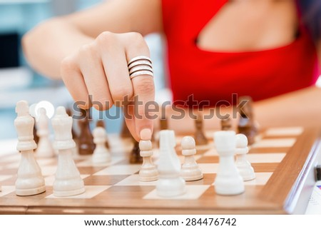 Business woman sitting in front of chess and planning - stock photo