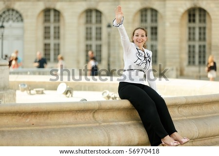 business woman sitting on big fountain edge and waving hand in hello sign - stock photo