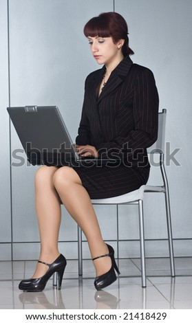 business woman sitting on chair with laptop - stock photo