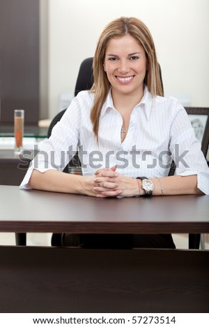 Business woman sitting on her desk at the office and smiling