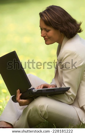 Business woman sitting on meadow, using laptop
