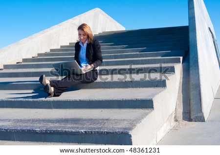 business woman sitting on the stairs with laptop on sunny day, wide - stock photo
