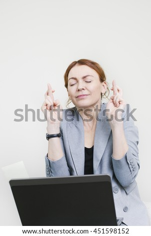 Business woman sitting with crossed fingers wishing good result in front of her laptop. Closed eyes business woman - stock photo