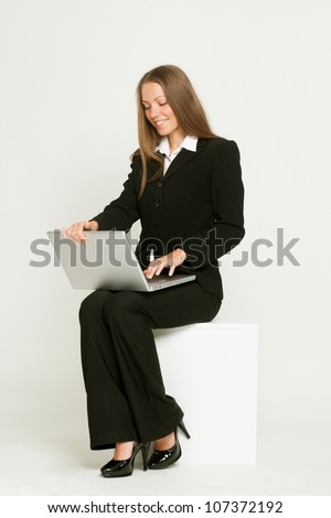 Business woman sitting with laptop computer on white - stock photo