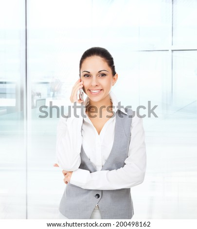 business woman smile cell phone call, talking on mobile cellphone, young businesswoman in modern office - stock photo