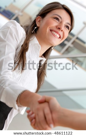 Business woman smiling and doing a handshake in the office - stock photo