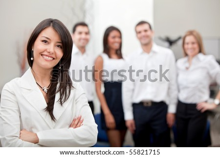 Business woman smiling with a group behind at the office