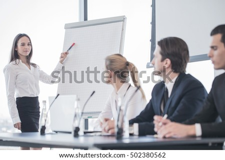 Business woman speaking at presentation and pointing to white board