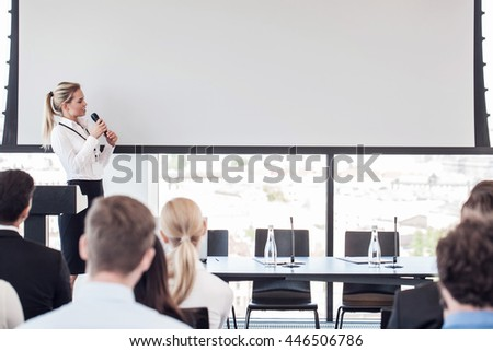 Business woman speaking at presentation in microphone in office - stock photo