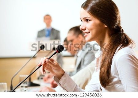 Business woman speaks into a microphone, communication businessmen at a conference - stock photo