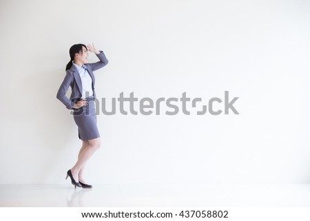 business woman stand and look something with white wall background, great for your design or text, asian
