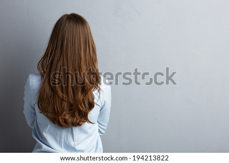 Business woman standing back against gray wall. Long hair - stock photo