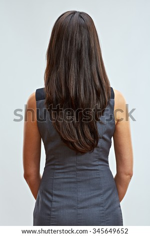 Business woman standing back with long hair. Studio isolated. Gray business dress code. - stock photo