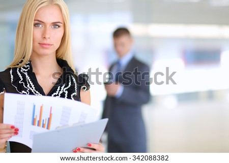 Business woman standing in foreground with a folder in her hands - stock photo