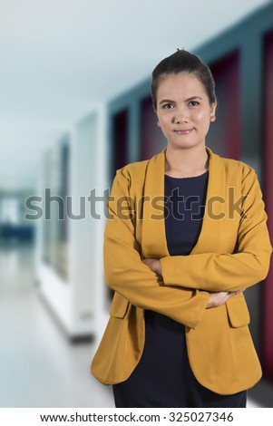 Business woman standing isolated grey wall background. Beautiful mixed race Thailand Asian-Caucasian young female mode in suit. - stock photo