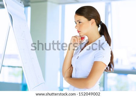 Business woman standing near a flipchart with his arms crossed - stock photo