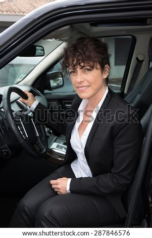 Business woman standing next to his car - stock photo