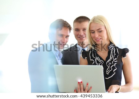Business woman standing with her staff in background at modern office