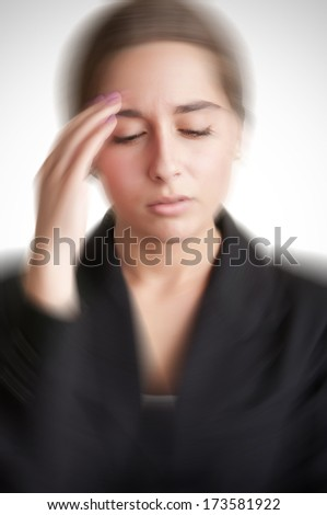 Business woman suffering from an headache, holding her hand to the head, with radial blur effect applied - stock photo