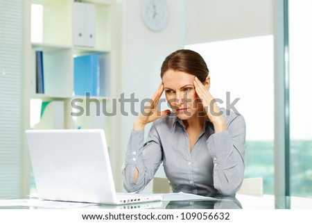 Business woman suffering from headache - stock photo
