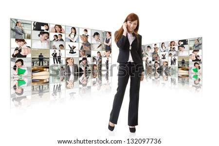 Business woman talk on cellphone in front of video wall. Business conferencing and global communications concept.