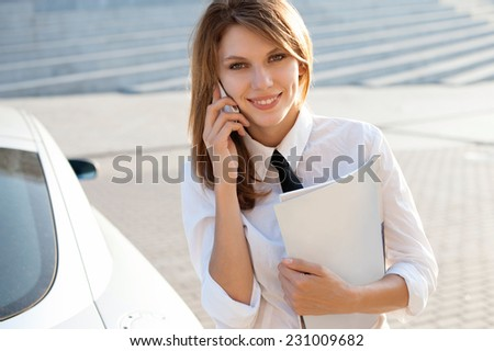 Business woman talking on her mobile phone. City business woman working / talkative woman in a white button down shirt with black tie  - stock photo