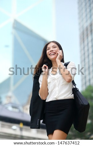 Business woman talking on phone outdoor, Hong Kong. Asian business people office worker talking on smartphone smiling happy. Young multiracial Chinese Asian / Caucasian female professional outside. - stock photo