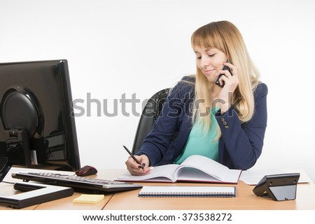 Business woman talking on the phone and writes in the book office - stock photo
