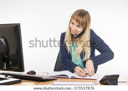 Business woman talking on the phone, record information in the office book and looked at the monitor - stock photo