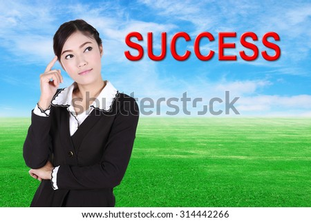"business woman thinking about ""success"" with green grass field and blue sky background"