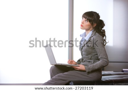 Business woman thinking in modern office with laptop