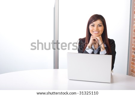 Business woman thinking in modern office with laptop - stock photo