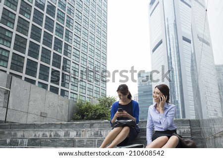 Business woman to talk happily sitting on the stairs - stock photo