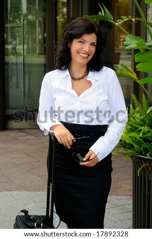 Business Woman Traveling With Her Rolling Luggage Outside Her Office - stock photo