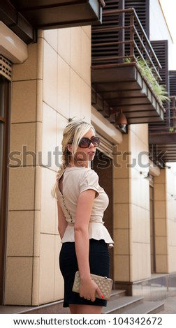 business woman turns around on the street in sunglasses - stock photo