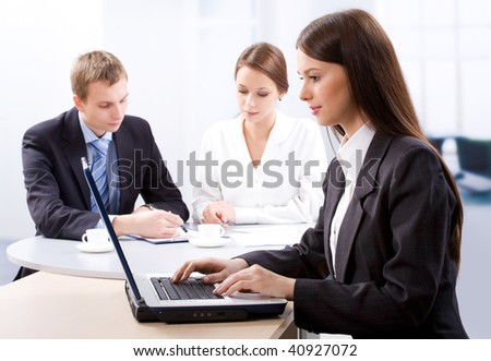 Business woman uses the laptop and her colleagues hold discussions