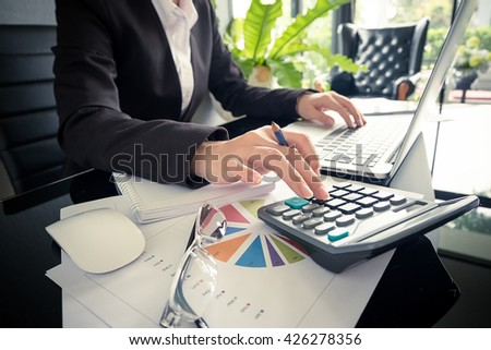 Business woman using a calculator to calculate the numbers on his desk in a office. - stock photo