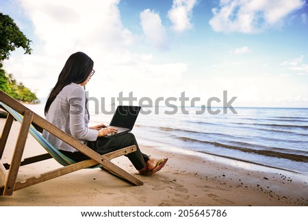 Business woman using a laptop beside the beach