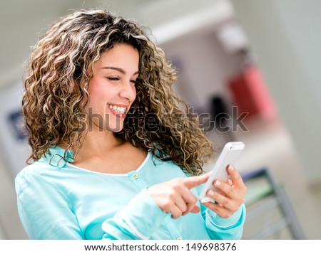 Business woman using a smart phone and smiling  - stock photo