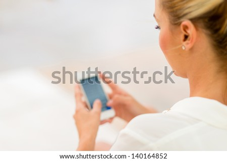 Business woman using app on a smart phone - stock photo