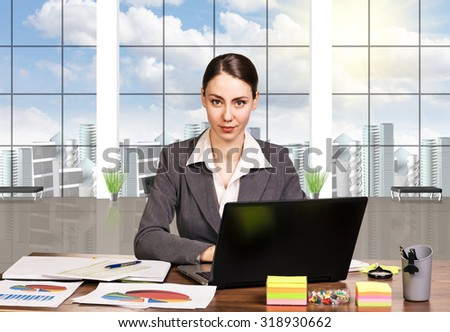 Business woman using laptop while sitting at her desk in the office. - stock photo