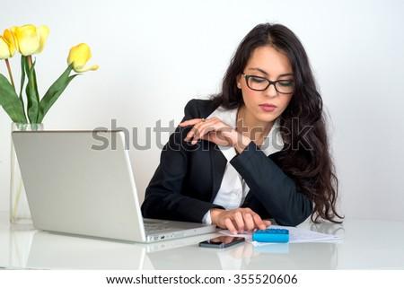 business woman using pocket calculator - stock photo