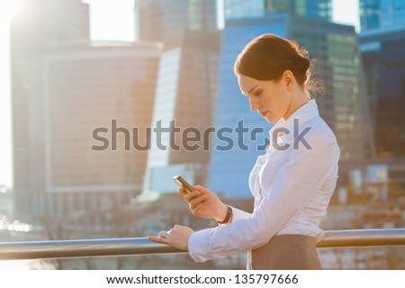 Business woman using smartphone. Sun beams, lens flare - stock photo