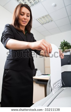 Business woman utilises documents in shredder - stock photo