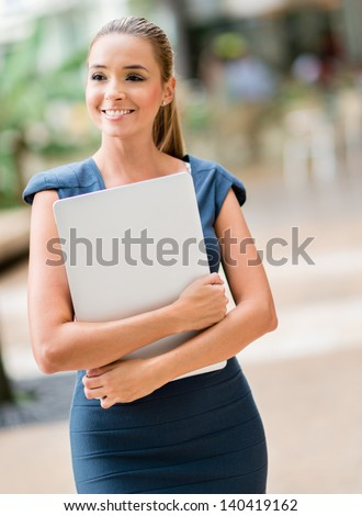Business woman walking outdoors holding a laptop