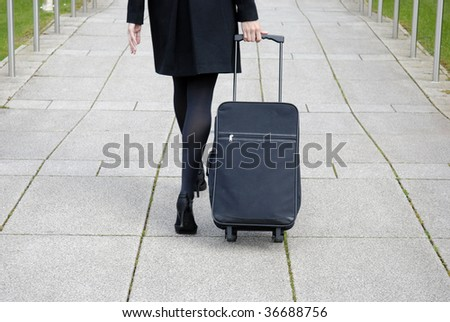 Business woman walking with black overnight case.