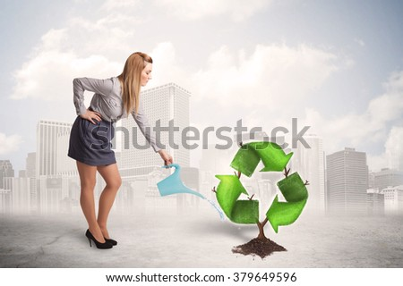 Business woman watering green recycle sign tree on city background concept - stock photo