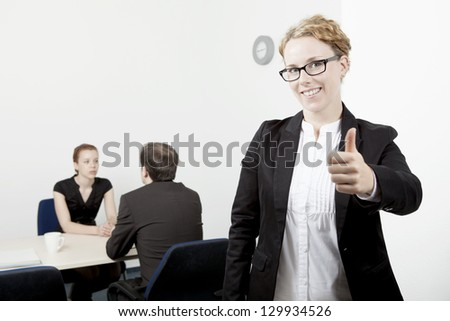 Business woman wearing glasses standing to the forefront while her colleagues work in the background giving a thumbs up of success and approval, conceptual of leadership , teamwork and authority