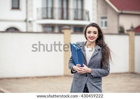 Business woman with a blue folder in hand waiting at the building